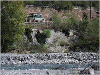 Fig. 3 -Érosion de berge menaçant plusieurs enjeux socio-économiques sur la Dora di Bardonecchia (Piémont- Italie): route, chemin de fer, réseau électrique.
